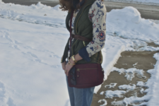With floral shirt, olive green vest, jeans and purple bag