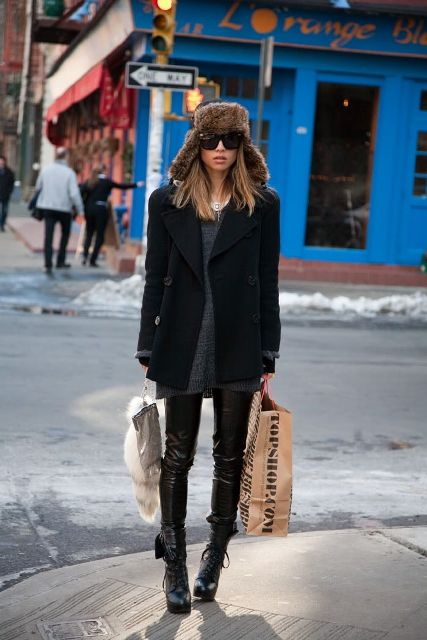 With gray sweater, black coat, leather pants and lace up boots