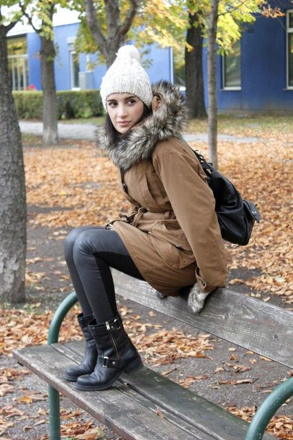 With leather pants, white beanie, brown parka coat and black backpack