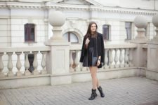 With leather skirt, black top and black jacket