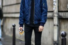 With navy blue puffer jacket, black pants, black boots and backpack