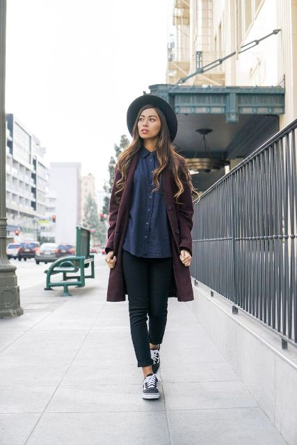 With navy blue shirt, crop jeans, sneakers and black hat