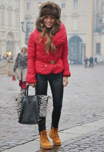 With red puffer jacket, black pants, printed tote and brown boots