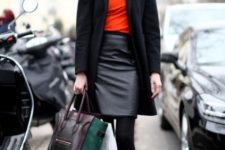 With red shirt, black leather skirt, ankle boots, black coat and two colored bag
