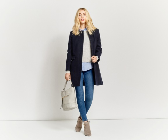 With shirt, beige sweater, skinny jeans, suede boots and light gray bag