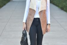 With white shirt, black pants, ankle boots and small bag