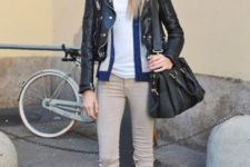 With white top, leather jacket, beige pants and black leather bag