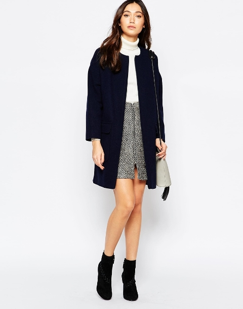 With white turtleneck sweater, tweed skirt, ankle boots and gray bag