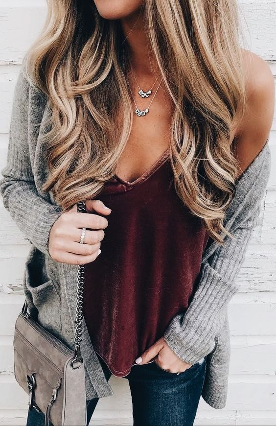 a burgundy velvet top, a grey cardigan, blue jeans and a grey bag