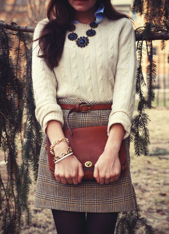 a cashmere cable knit sweater, a tweed mini skirt, a brown leather belt and a matching bag