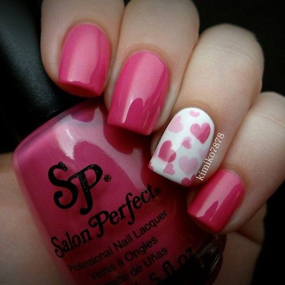 pink nails and an accent nail with pink hearts of different sizes
