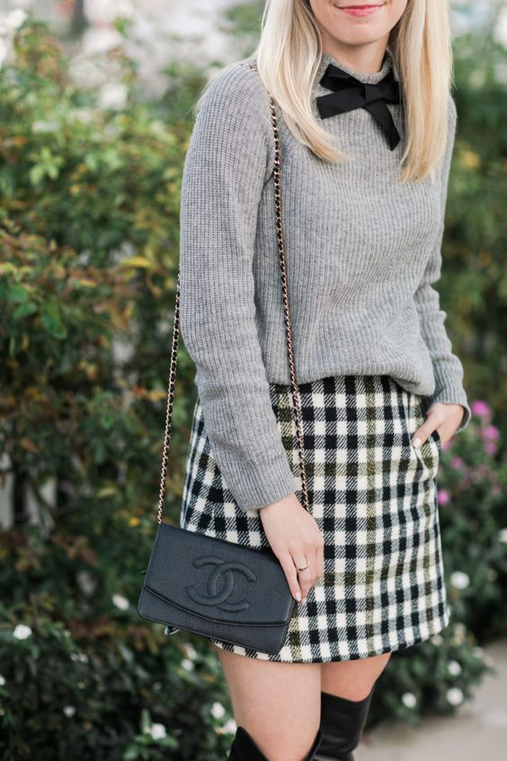 a grey cashmere sweater with a black bow, a checked mini skirt and tall boots