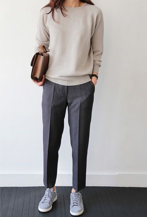 a neutral cashmere sweater, grey trousers, grey sneakers and a brown leather bag for a relaxed work look