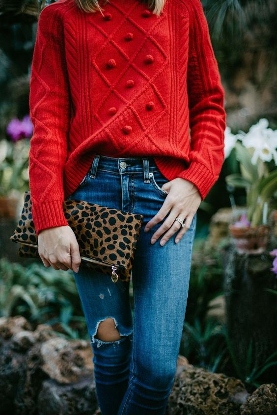 a red patterned sweater, ripped jeans and a leopard print clutch