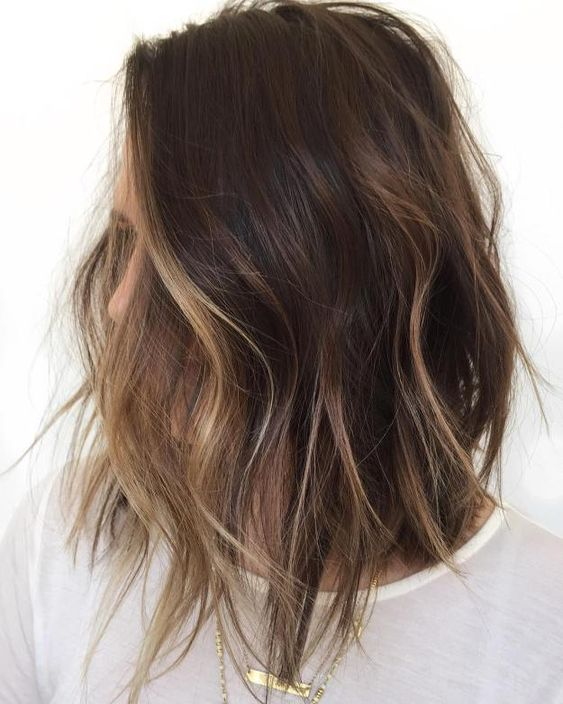 a shaggy brunette bob with face-framing bronde balayage to highlight the face