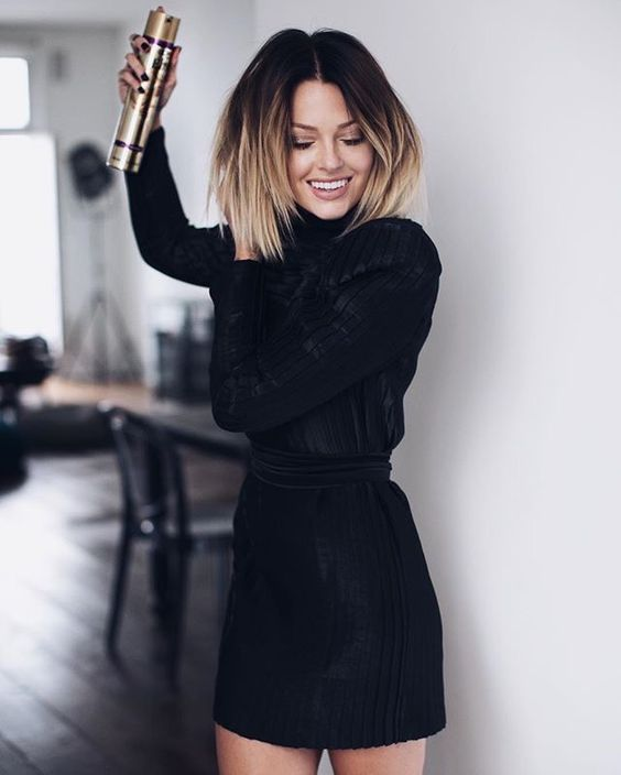 a short layered bob haircut with dark roots and bronde ends is a bold statement