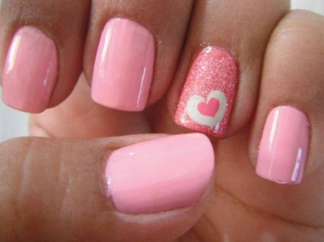 pink nails with a glitter accent one and a heart sticker for a bold look