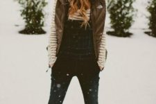 05 a striped top, a denim overall, a puff vest, snow boots and a beanie