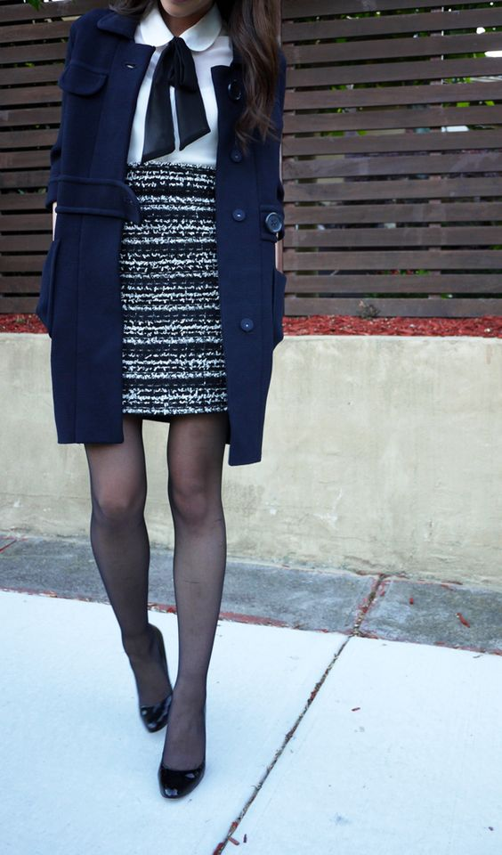 a tweed pencil skirt, a white peter pan top with a black bow, a navy coat