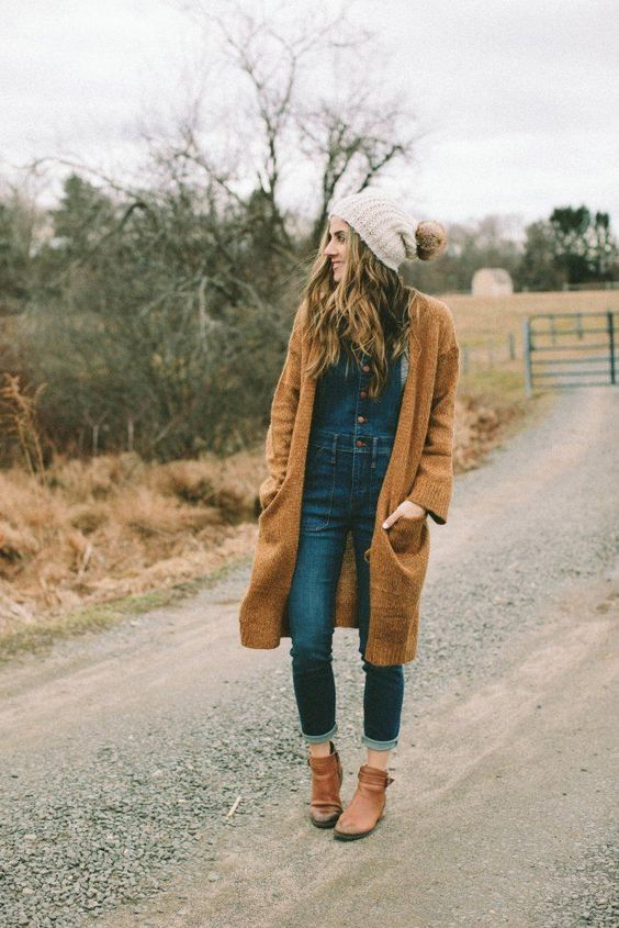 a denim overall on buttons, a top, a rust-colored cardigan, matching booties and a beanie