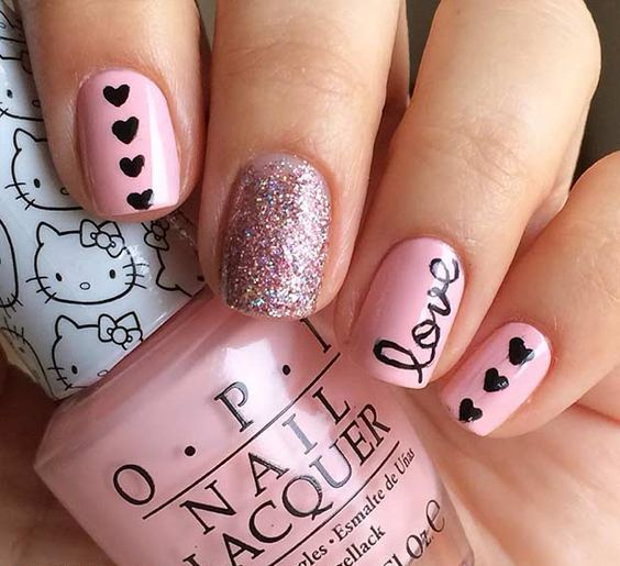 a pink manicure with glitter, little black hearts and LOVE letters