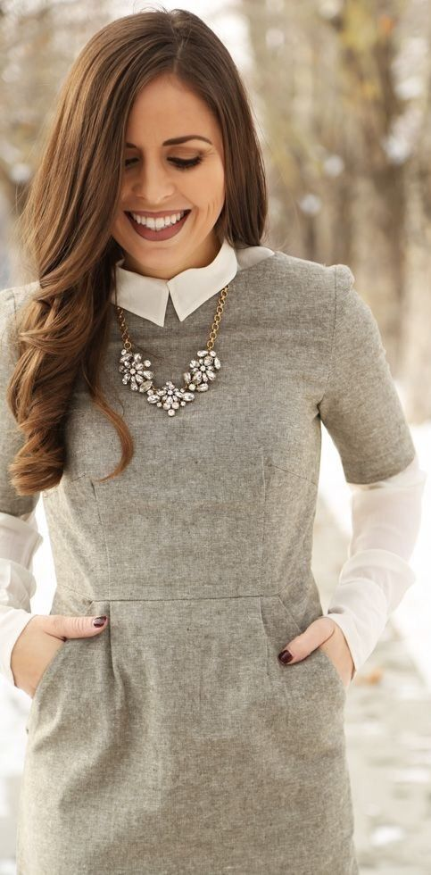 a white long sleeve shirt, a grey tweed dress and a statement necklace