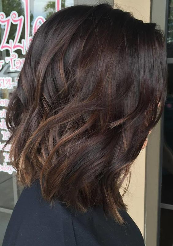 dark plum wavy hair with subtle bronde balayage to make the look more eye-catchy
