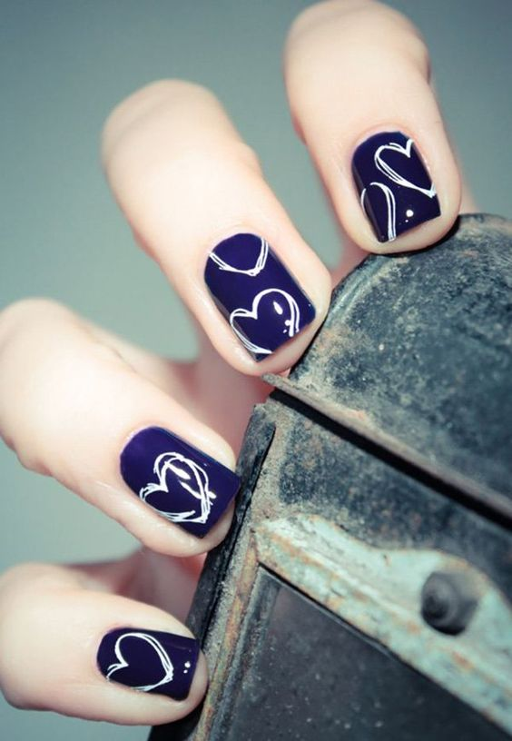 navy nails with white nail polish hearts for a bold and cute look