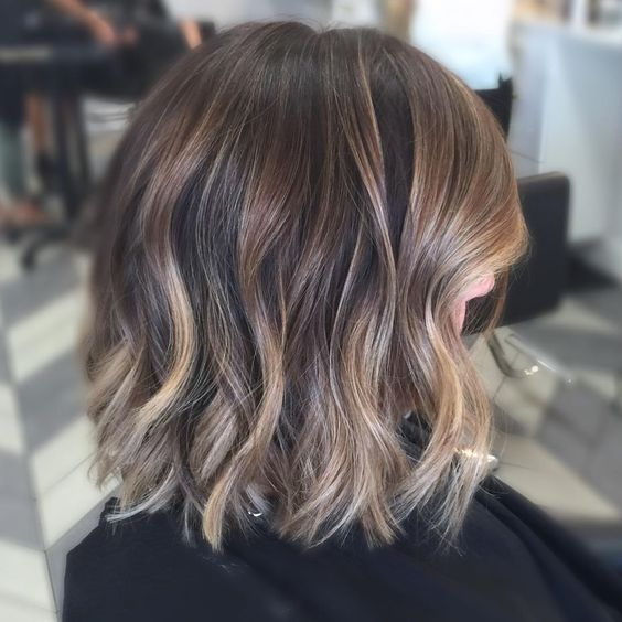 short brunette hair with gold balayage and light waves looks super chic