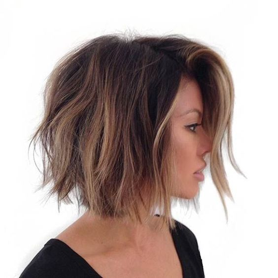 a brown short bob with brown balayage highlights and beachy waves for a trendy look
