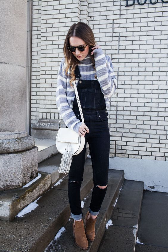 a dark denim overall with ripped parts, a striped top, brown booties and a neutral bag