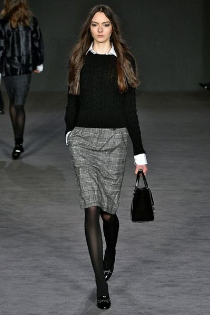 a white shirt, a black sweater over it, a tweed knee skirt, black tights and shoes