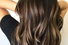 09 dark wavy hair with subtle blonde balayage to add eye-catchiness to the look