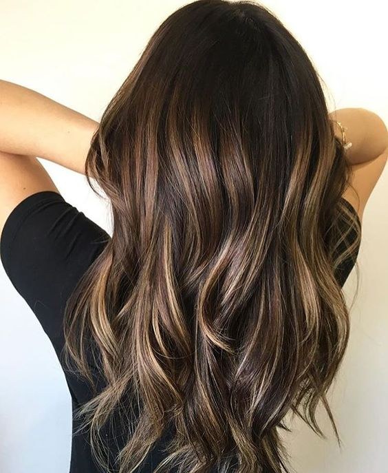 dark wavy hair with subtle blonde balayage to add eye-catchiness to the look