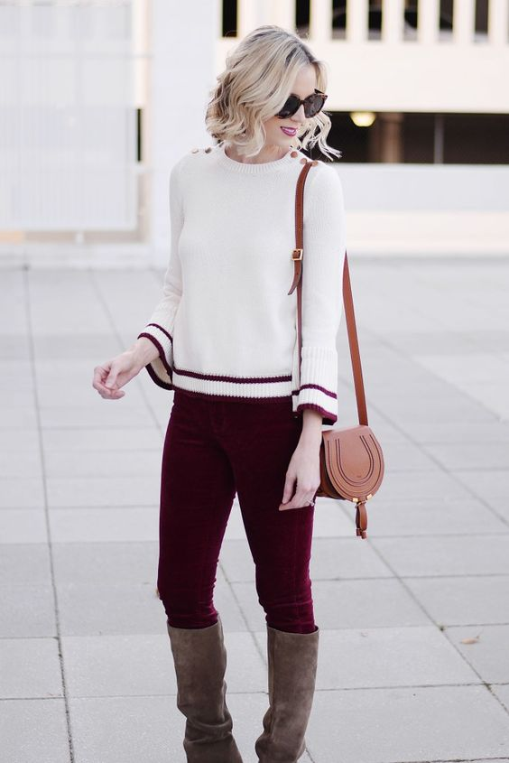 grey boots, plum colored velvet pants, a white sweater with a red trim and a bag
