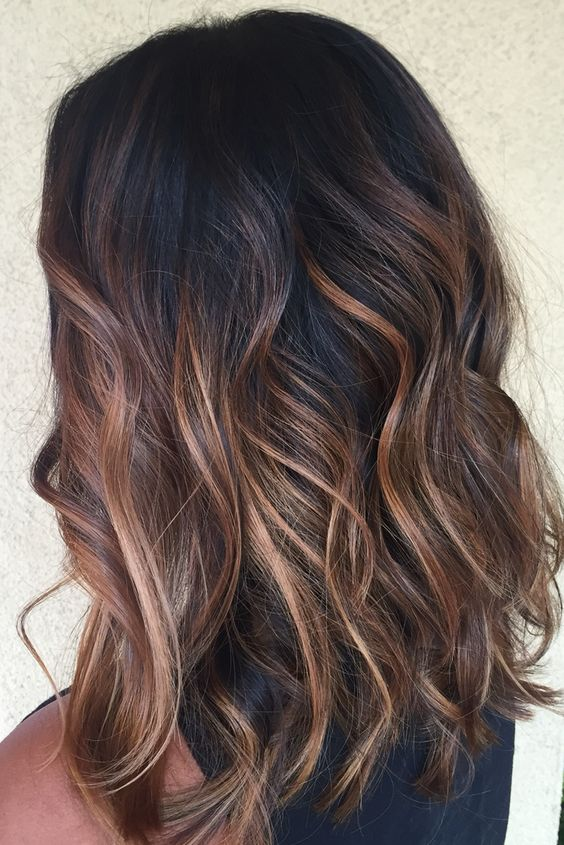 black hair with red and caramel balayage to add a warm touch and chic