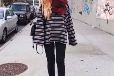 10 black skinnies, a striped oversized sweater, black shoes and a plum-colored scarf