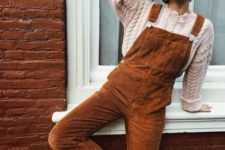 11 a cable knit neutral sweate and beanie, a rust-colored overall and white sneakers