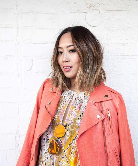 a short dark wavy bob with bronde balayage higlhlights that create a volume