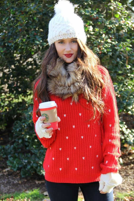 black jeans, a red heart print sweater, a faux fur scarf and a white beanie