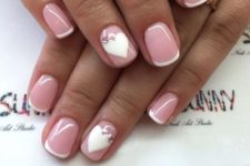 12 French manicure with white nail hearts topped with rhinestones for a stylish look