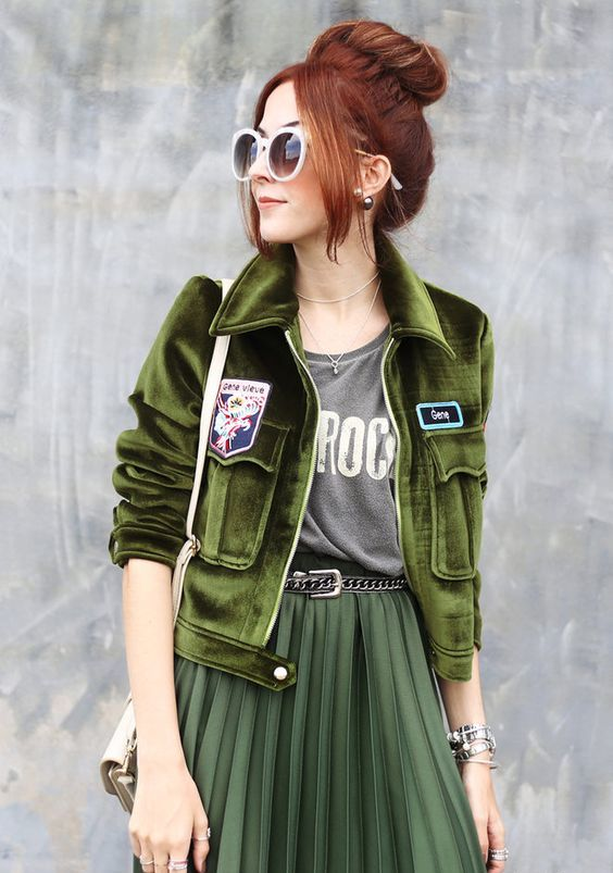 a green velvet pilot jacket, a forest green midi pleated skirt and a printed tee