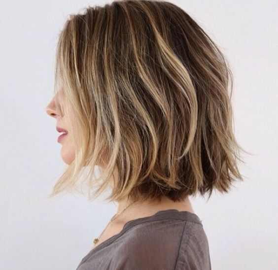 a wavy short brown bob with blonde balayage highlights for creating a volume