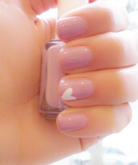 pink nails with one single white heart for a subtle touch