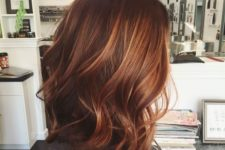 16 red wavy hair with lighter fiery orange balayage that makes the look bolder