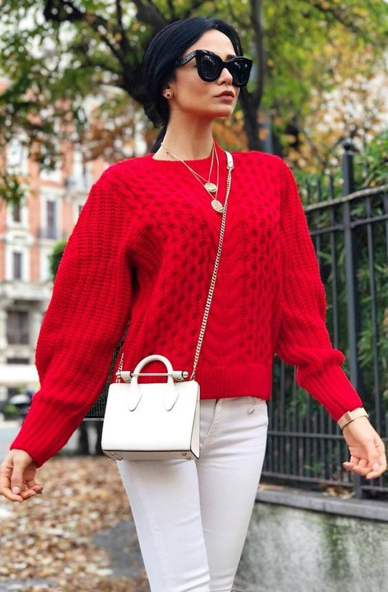 white jeans, a red sweater, layered necklaces and a small crossbody bag