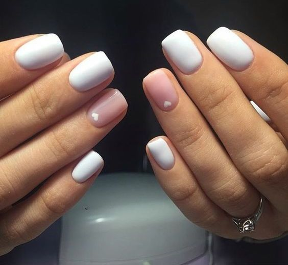 white matte short nails with a blush accent and little white hearts on them