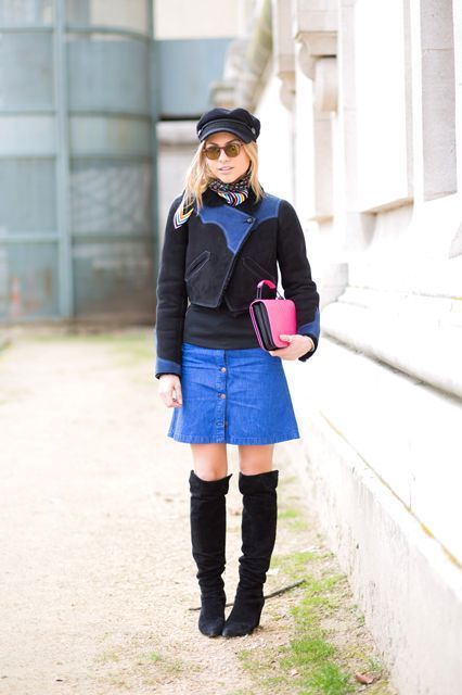 With black shirt, black and blue jacket, cap, over the knee boots and pink clutch