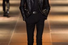 With black shirt, black leather jacket, skinny trousers and leather boots