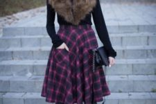 With black shirt, fur collar, high boots and black clutch